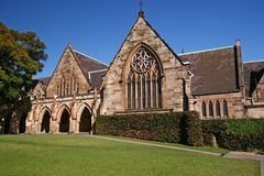 Gothic revival style facade of classic and historic stone St Paul's College on sloped grass field at University of Sydney,. Heritage and classical building stock photo