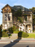 Heritage House in Santa Cruz Ca. Victorian house Santa Cruz California, tasetful combination of shades of brown creme and yellow. Large palm tree in front Royalty Free Stock Photo