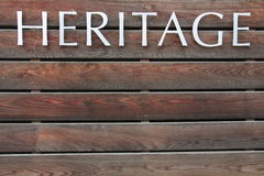 HERITAGE text on wood background. HERITAGE text on brown wood background Royalty Free Stock Image