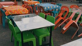 Herkömmliche Plastiktabellen und Stühle in einem der billigsten Cafés in Asien Mehrfarbige Polyäthylentischdecken an stock footage
