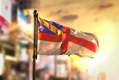 Herm Flag Against City Blurred Background At Sunrise Backlight. Sky Royalty Free Stock Photography