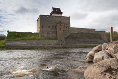 Hermann Castle on the Narva river and the russian border-marking pole. Royalty Free Stock Photo