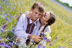 Hermana adolescente y pequeño hermano junto en campos de trigo del verano Fotos de archivo