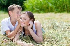 Hermana adolescente y pequeño hermano que se sientan en el heno Fotos de archivo libres de regalías