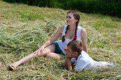 Hermana adolescente y pequeño hermano que se sientan en el heno Foto de archivo