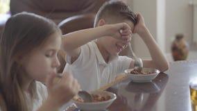 Hermana adorable del retrato y su gemelo cansado del hermano que intentan comer las gachas de avena o los copos de maíz para el d almacen de metraje de vídeo