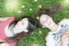 Hermana al adolescente de las hermanas que miente en las flores de la hierba Fotografía de archivo libre de regalías
