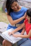 Hermana china y pequeña hermosa con la computadora portátil imágenes de archivo libres de regalías