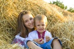 Hermana con el hermano menor en el heno Imagen de archivo libre de regalías