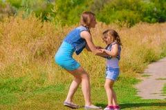Hermana de las muchachas en un campo con las flores Fotografía de archivo libre de regalías