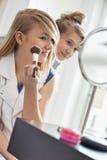 Hermana de observación de la muchacha que aplica maquillaje delante del espejo en casa Imagen de archivo