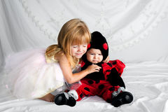 Hermana Dressed de Hugs Her Younger de la hermana de Blissfilled como mariquita Fotos de archivo libres de regalías
