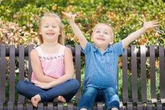 Hermana emocionada y Brother Having Fun On el banco en un parque fotos de archivo