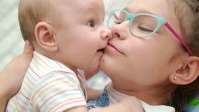 Hermana feliz que besa al hermano del bebé Ciérrese para arriba de bebé lindo del beso de la muchacha almacen de metraje de vídeo