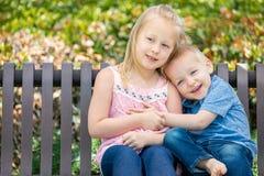 Hermana grande y poco Brother Hugging On un banco en el parque imágenes de archivo libres de regalías