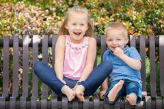 Hermana joven y Brother Having Fun On el banco en el parque fotografía de archivo libre de regalías