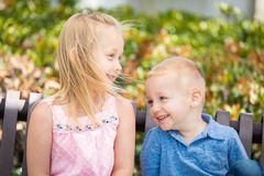 Hermana joven y Brother Having Fun On el banco en el parque imágenes de archivo libres de regalías