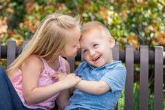 Hermana joven y Brother Having Fun On un banco en el parque imagen de archivo