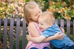 Hermana joven y Brother Hugging On un banco en el parque fotografía de archivo libre de regalías