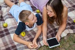Hermana joven y hermano que se acuestan y trabajo con la tableta foto de archivo