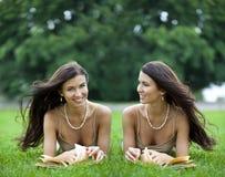 Hermana a las mujeres que leen un libro al aire libre Fotografía de archivo
