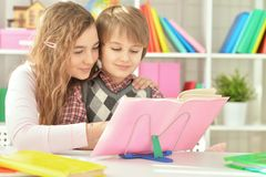 Hermana que ayuda a su hermano con la preparación Imágenes de archivo libres de regalías