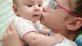 Hermana que besa al hermano del bebé Amor dulce de la familia Una más vieja hermana que abraza al niño lindo almacen de metraje de vídeo