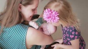 Hermana que besa a su hermano recién nacido que su mamá está sosteniendo mientras que se sienta en una mecedora metrajes