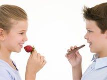 Hermana que come la fresa comiendo del hermano Imagen de archivo libre de regalías