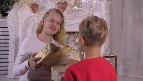Hermana que da el regalo de la Navidad a poco hermano en fondo decorativo de la chimenea almacen de metraje de vídeo