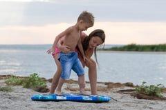 Hermana que enseña su hermano a cómo practicar surf Imagen de archivo libre de regalías