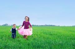 Hermana runing con su brather en la hierba Foto de archivo libre de regalías