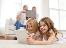 Hermana sonriente con PC y los padres de la tableta encendido detrás Foto de archivo
