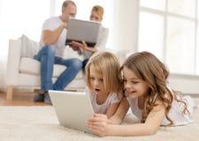 Hermana sonriente con PC y los padres de la tableta encendido detrás Imágenes de archivo libres de regalías