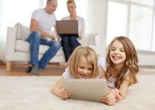 Hermana sonriente con PC y los padres de la tableta encendido detrás Fotografía de archivo