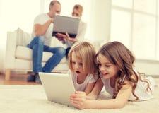 Hermana sonriente con PC y los padres de la tableta encendido detrás Fotografía de archivo libre de regalías