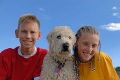 Hermana y hermano con el perro Imágenes de archivo libres de regalías