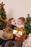 Hermana y hermano debajo del árbol de Christms Foto de archivo libre de regalías