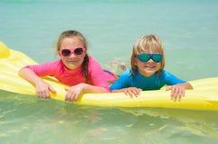 Hermana y hermano que juegan con el colchón de aire en la playa Fotos de archivo libres de regalías