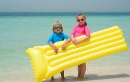 Hermana y hermano que juegan con el colchón de aire en la playa Fotografía de archivo libre de regalías