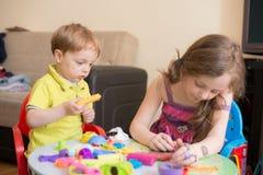 Hermana y hermano que juegan en casa Foto de archivo libre de regalías