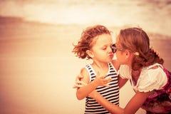 Hermana y hermano que juegan en la playa en el tiempo del día Foto de archivo