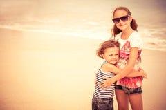 Hermana y hermano que juegan en la playa en el tiempo del día Fotografía de archivo