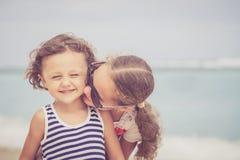 Hermana y hermano que juegan en la playa en el tiempo del día Imagen de archivo libre de regalías