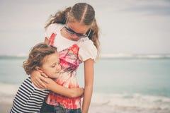 Hermana y hermano que juegan en la playa en el tiempo del día Imagen de archivo