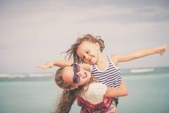 Hermana y hermano que juegan en la playa en el tiempo del día Imagenes de archivo