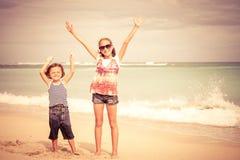 Hermana y hermano que juegan en la playa en el tiempo del día Foto de archivo libre de regalías