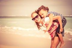 Hermana y hermano que juegan en la playa en el tiempo del día Fotos de archivo