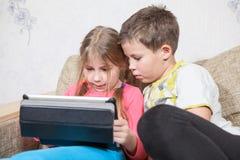 Hermana y hermano que se divierten con PC de la tableta mientras que se sienta en el sofá junto Fotografía de archivo libre de regalías