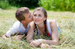 Hermana y pequeño hermano que mienten en el heno en fondo del verano al aire libre Fotografía de archivo